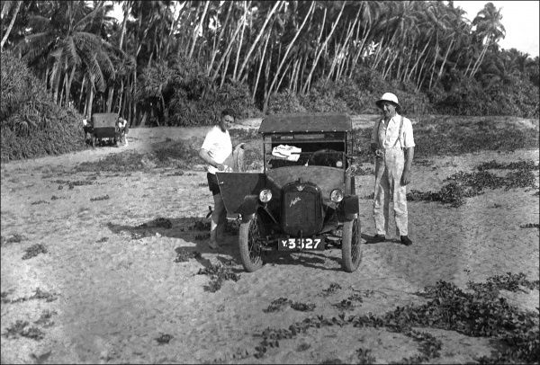 Men on the beach, about to bathe with their Austin 7