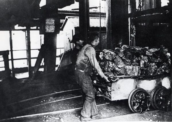 Two men hauling a dram (truck) full of coal from a cage at the pithead of the Elliot Colliery, New Tredegar, Rhymney Valley, South Wales