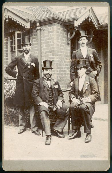 Four men, two seated, two standing, in top hats and with decorations pinned to their lapels, pose for a photograph outside a brick house