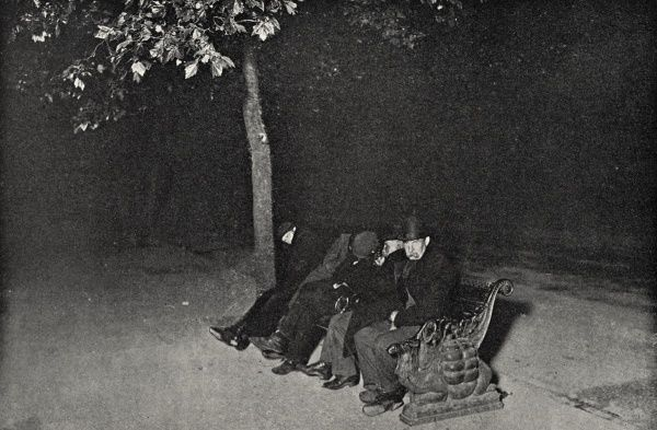 A group of men try to make themselves comfortable enough to sleep on a bench on the Embankment in Central London