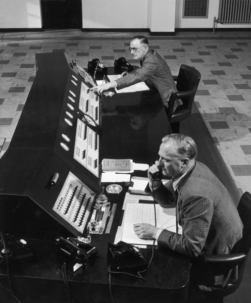 Two men working at a telephone switchboard desk in a factory. Photograph by Heinz Zinram