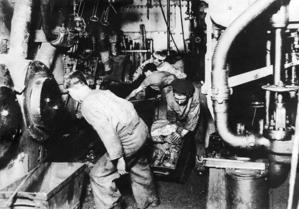 Men at work loading coal in the engine room of a ship during the First World War. Date: 1914-1918