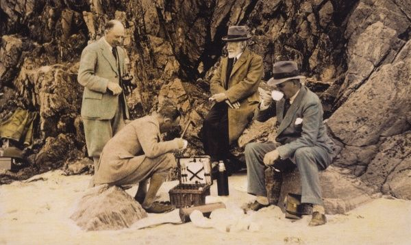 Four gentlemen picnic on a rocky shore. Date: 1920s