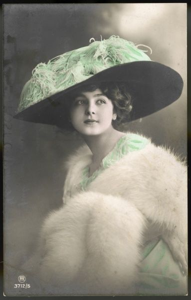"Beautiful young lady wearing a rather large, plume laden hat - a style that became known as the ""Merry Widow"" after a hat worn by Lily Elsie in the operetta of the same name"