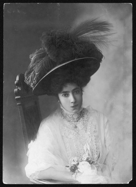 A large, feather-laden hat with ostrich plumes & aigrette (egret) worn atop a padded hairstyle by a tight-lipped lady in a high- necked lace bodice or blouse