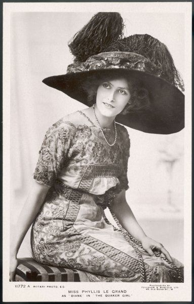 "Actress Phyllis Le Grand as Diane in ""The Quaker Girl"" wears a hat in the style of that worn by Lily Elsie in ""The Merry Widow"", with a large crown & ostrich plumes"