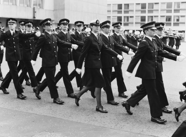 A group of Metropolitan Police cadets on parade, with a brass band playing in the background