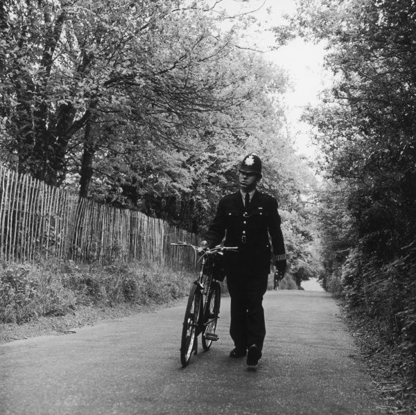 A Metropolitan Police officer on the beat, wheeling his bicycle along a country lane in a rural part of London