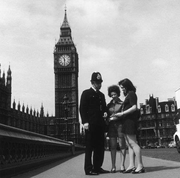 A Metropolitan Police officer giving directions to two young women on Westminster Bridge, Central London