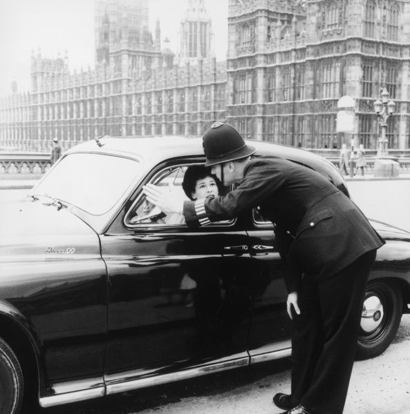 A Metropolitan Police officer in Central London, giving directions to a young woman in a Rover 90 saloon car, with the Houses of Parliament in the background