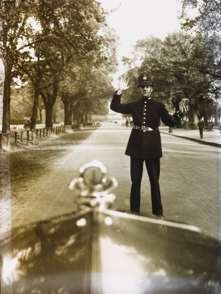 A Metropolitan Police officer on duty in a London park holds up his right hand to stop a motorist. He is holding a small machine in his left hand, possibly used for measuring speed of travel