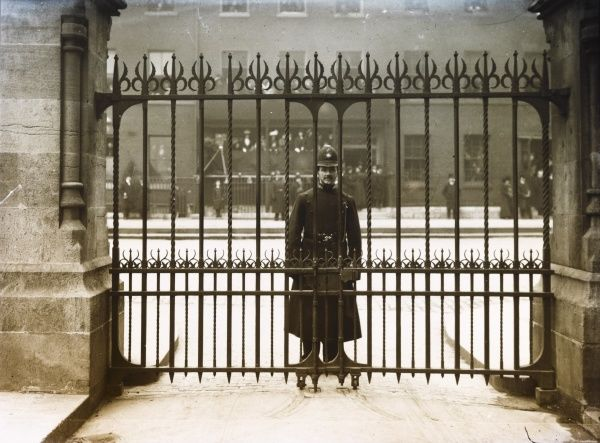 A Metropolitan Police officer on duty on a London street looks straight at the photographer through a set of spiked iron gates