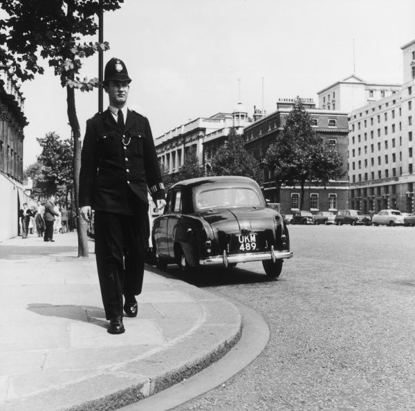 A Metropolitan Police officer on the beat somewhere in Central London, approaching a street corner