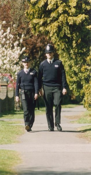 Two Metropolitan Police officers, a PC and a WPC, walking along a suburban pathway in a residential area of London. The woman has a large walkie talkie radio at her waist. They are wearing 'unisex' uniforms, ie trousers and V-necked jumpers