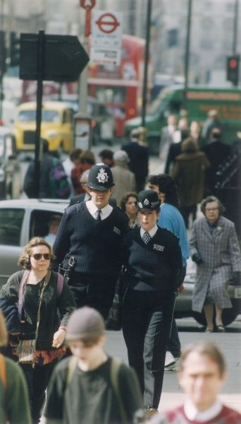 Two Metropolitan Police officers, a PC and a WPC, walking along a busy urban street in Central London. They both carry a set of handcuffs at their waists. They are wearing 'unisex' uniforms, ie trousers and V-necked jumpers