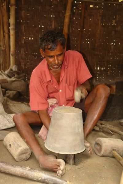 A metal worker makes a brass pot by traditional methods at Matiari, a village in West Bengal, India. Date: 2007