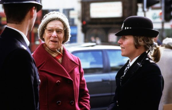 Two Metropolitan Police officers, one male, one female, chatting on a London street with an elderly member of the public
