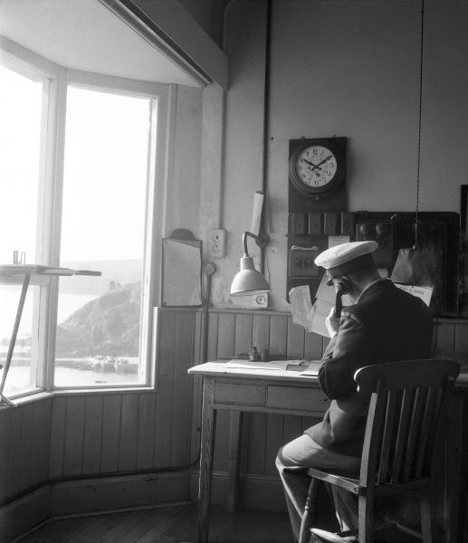 The uniformed coastguard at Mevagissey, Cornwall, England, sits in his office and takes a phone call, perhaps an emergency call. Mevagissey is a small, fishing village with a colourful history of boat building and smuggling