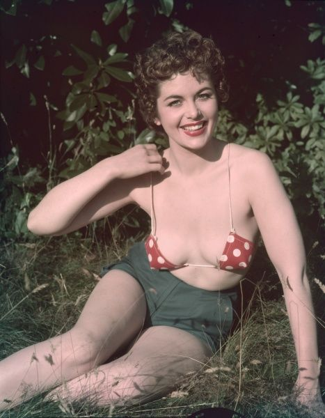 A fresh faced model with chestnut curls and a beaming smile adjusts the narrow spaghetti straps to her red & white polka dot bikini top which she wears with shorts