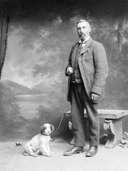A middle aged man poses in the photographer's studio, Mid Wales, with a spaniel puppy on a chain. There is a stone bench behind him, and a painted backdrop of a lake and mountains