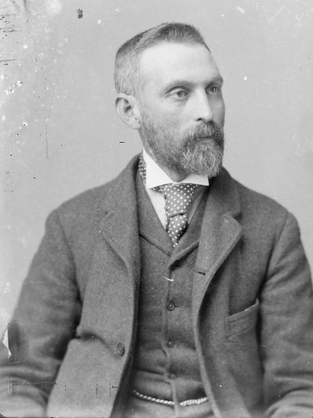A middle aged man poses in the photographer's studio, Mid Wales. He has a pointed beard, and wears a three-piece suit, with a spotty tie and wing collar