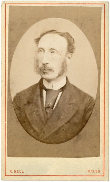 A middle-aged Victorian man with whiskers and a long face. He is wearing a wide-lapelled jacket and a large tie with a tiepin
