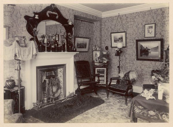 The corner of a middle-class sitting room, with ornaments in the characteristic cast- iron fireplace with its tile surround, and on the mantel, and indeed on everything