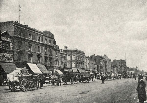 A view of the Mile End Road in the East End of London. A variety of horse-drawn vehicles stand in front of the shops at the far side of the road