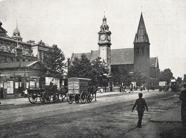 A view of the Mile End Road in the East End of London. A horse-drawn tram and various trade carts can be seen. St Benet's Church stands at the centre right of the scene with the People's Palace to the left
