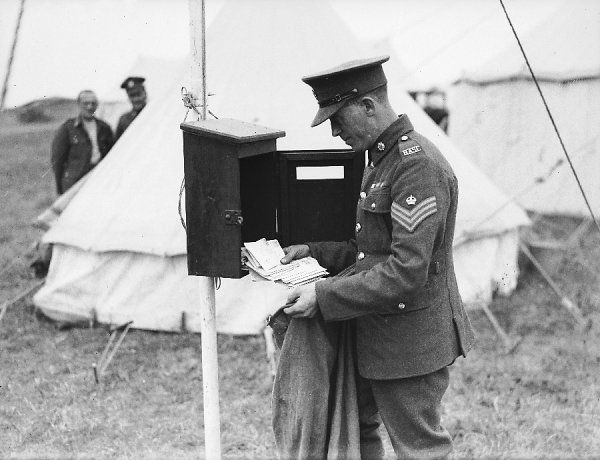A military postman for the British army collecting post from a mail box on an army camp site