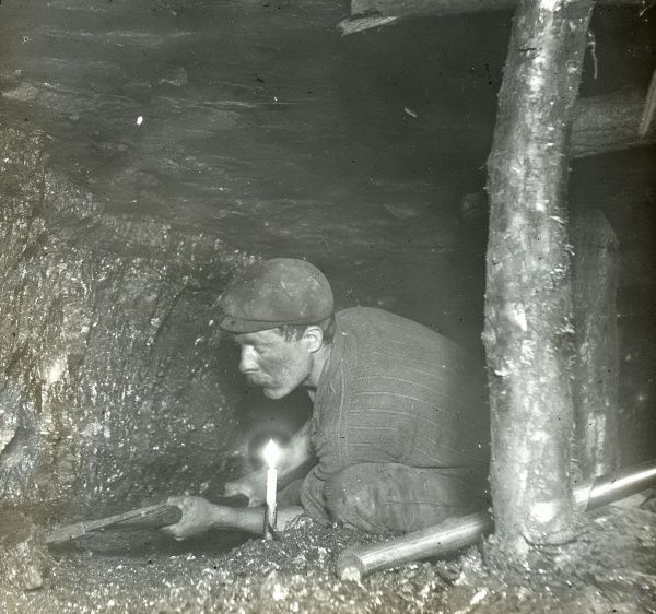 A miner undercutting or holing the coal in a narrow seam, Plas y Coed Level, South Wales. A solitary candle provides him with light