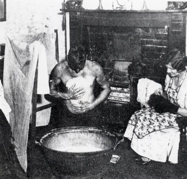A South Wales miner washes at a tin bath in front of the fire, while his wife sits mending socks