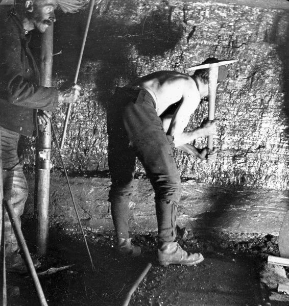 A miner, stripped to the waist, working at the coalface with a pick, in a mine in South Wales