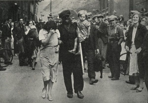 A black-faced miner, carrying his small daughter, his wife shielding her face, at Fernhill in the Rhondda. He has just emerged from 292 hours underground in a 'stay-in' miners' strike at Fernhill Colliery. He is watched by a throng of local people