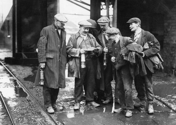 A group of British coal miners clutching their lamps have a good chuckle at a letter. Date: 1930s