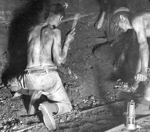 Two miners, stripped to the waist, working at the coalface in a coal seam in South Wales