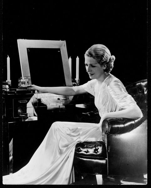 A graceful & elegant woman sits on an upholstered leather chair at a stylish art deco mirrored dressing table with a bottle of scent, candlesticks & looking glass