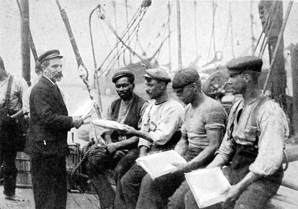 Photograph showing a Mission to Seamen Chaplain distributing papers and magazines to a merchant ship crew, on their vessel, 1906. Mission boats were at work in many of the world's largest ports, at this time. They visited ships to hold church services