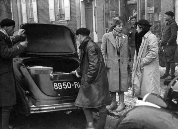 MADAME VILLIERS DE LA NOUE, (right), sister of the famous aviator GEORGE-MARIE GUYNEMER, standing on a snowy pavement with a female companion while two men sort out her car boot! Date: 1930s