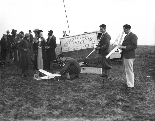 Men of the Brighton and District Model Aircraft Club with their model aeroplanes, attract the attention of women and boys