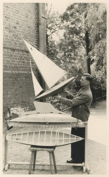 Model boat builder aholding up a finished example of his craft