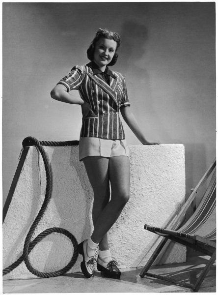 Young model wears white linen shorts and a striped, short- sleeved, double-breasted linen jacket. She also wears a pair of thick soled shoes laced up with cord