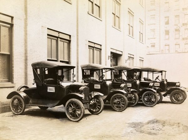 Automobile (Cars). Fleet of four Model T Fords parked outside behind a building for salesmen of Peter Doelger's Healthful Beverage