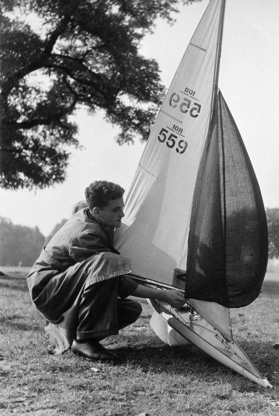 A man with his model yacht which he is probably preparing to sail Date: 1950s