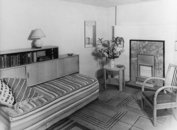 A 'modern' Art Deco style bedroom, with a practical divan sofa, simple bookcase and stylish gas fireplace. Date: 1930s