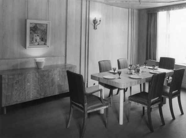 A 'modern' domestic dining room. Nowadays the table and chairs would be more suitable for a board room than a home! Date: 1930s