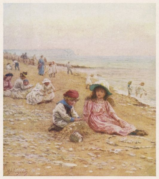 While a boy builds a sandcastle on the beach at Sandown, Isle of Wight, his sister watches somewhat disparagingly