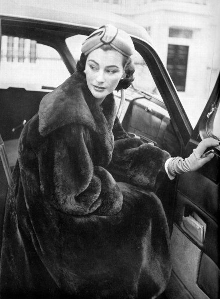 Dressed for Christmas shopping, a model wears a loose-fitting, swing-backed nutria coat from Molho of Brook Street. Date: 1953