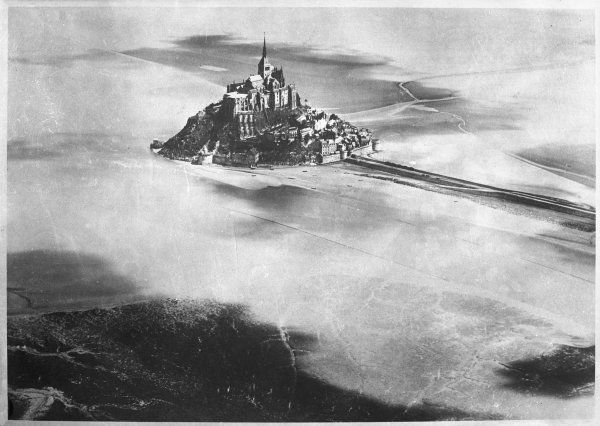 An aerial view of Mont St. Michel, Normandy, France, showing the dramatic monastery, with its steeple, peeping through the clouds