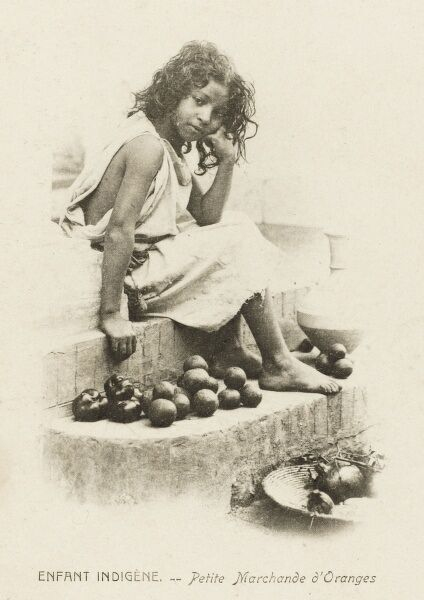 A young Moorish girls sitting on some steps and selling oranges. She wears a very tired and bored expression